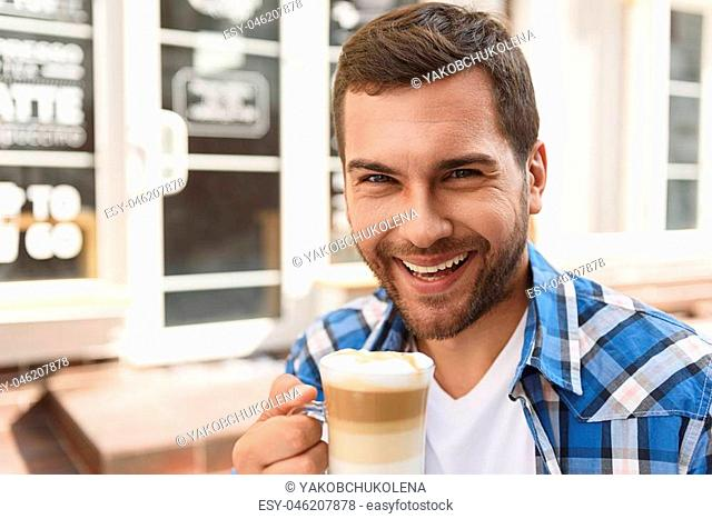 Every great day starts with good cup of coffee. Close up of smiling attractive guy looking at camera and holding cup of latte in his hand