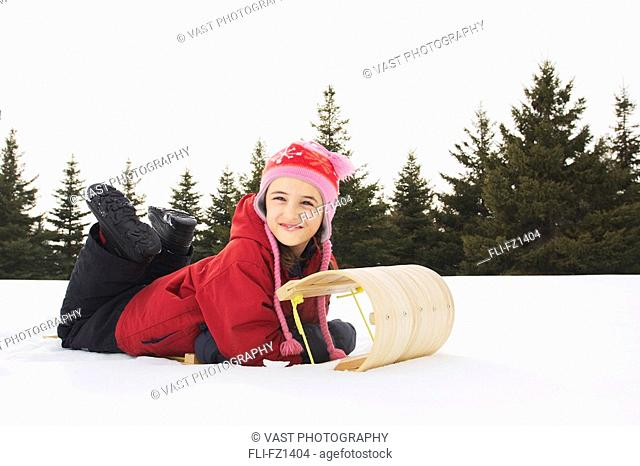 Young girl laying on sled, King City, Ontario