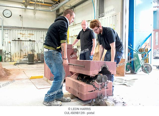 Male foundry workers lifting mould from bronze sculpture in bronze foundry