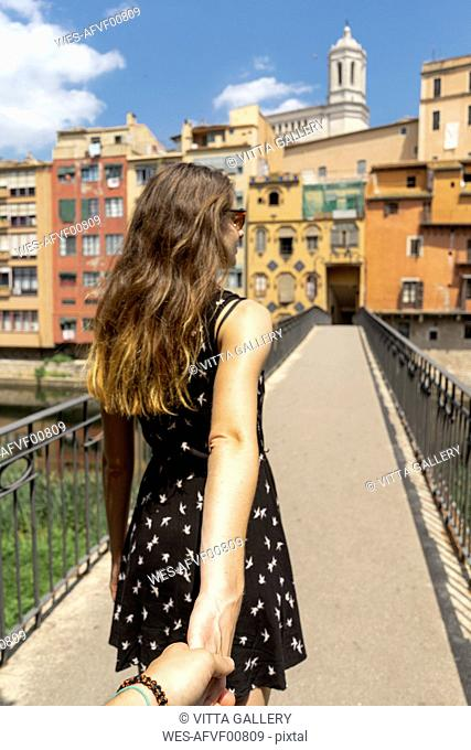 Spain, Girona, woman holding man's hand walking in the city