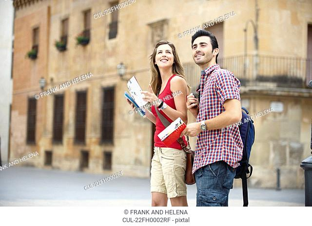 Couple with guidebooks in city square