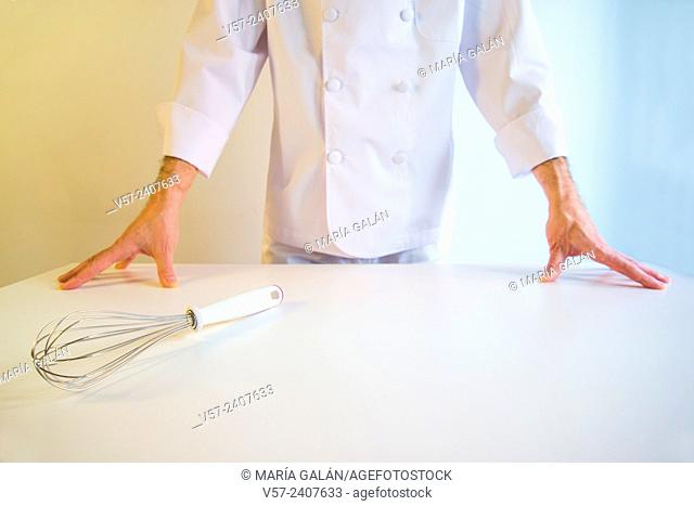 Cook behind a white table, hands on the table and whisk in the forefront