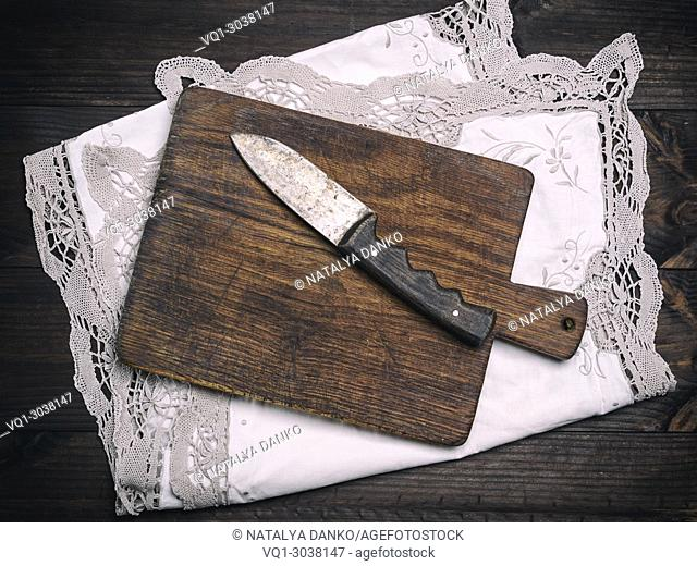 old brown wooden cutting board with handle and knife on white textile napkin with lace, top view