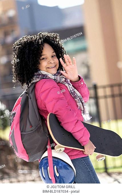 African American girl carrying skateboard outdoors