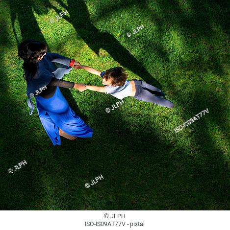 Mother swinging son around, outdoors, elevated view