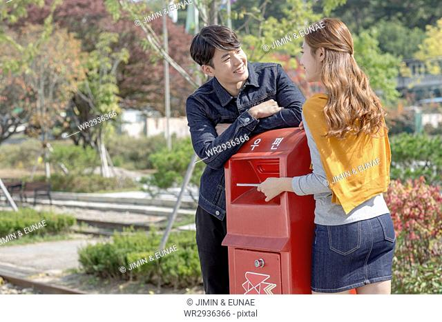 Young smiling couple travelers at postbox