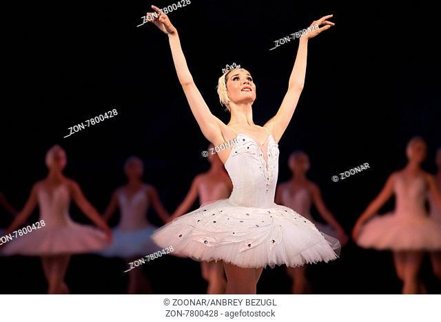 Prima ballerina white swan on stage dancing gracefully against other dancers. Ballet Swan Lake, the Opera House in Kiev, Ukraine
