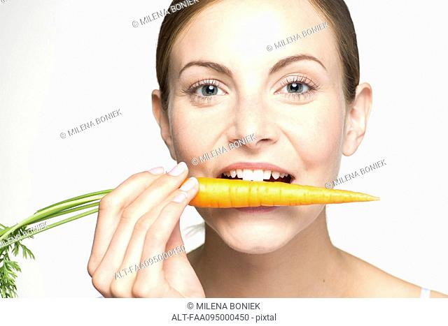 Young woman biting into carrot, portrait