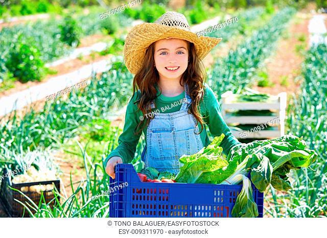 Litte kid farmer girl in vegetables harvest at orchard