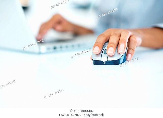 Closeup of laptop keypad with female hands operating mouse