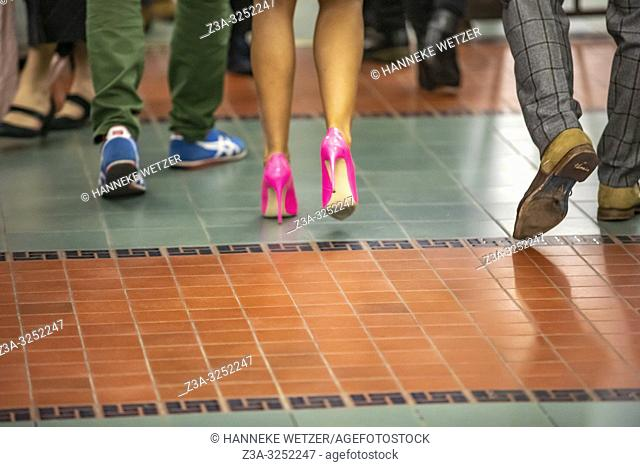 Woman with pink high heels walking in the middel of two men