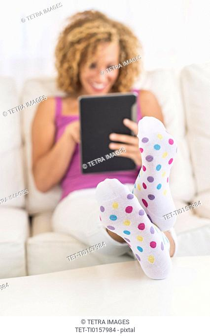 Young woman sitting on sofa with digital tablet