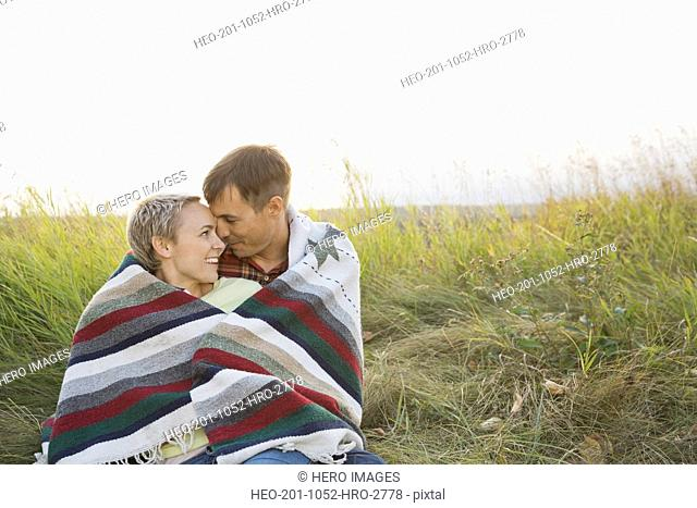 Happy couple wrapped in blanket at field