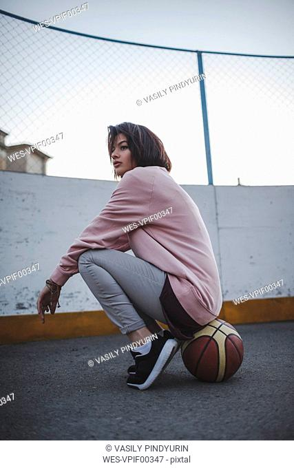 Young woman sitting on basketball outdoors