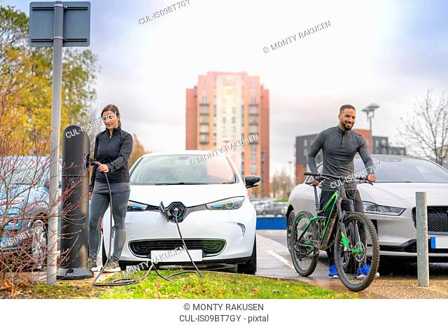 Man and woman with mountain bike at electric car charging point, Manchester, UK