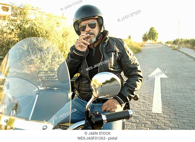 Portrait of cool biker wearing helmet and sunglasses sitting on his sidecar motorcycle smoking cigarette