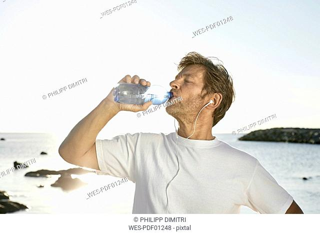 Mature man drinking water after jogging on the beach