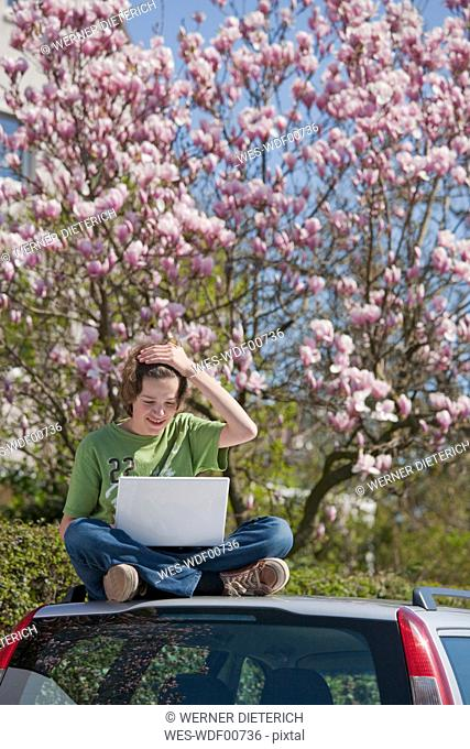 Germany, Boy sitting on car roof and using laptop with magnolia tree in background