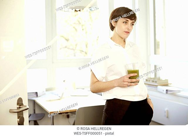 Daydreaming woman with glass of green smoothie in an office