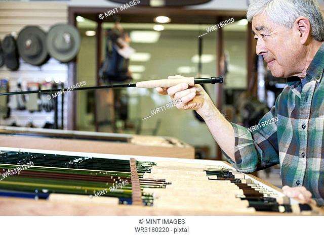 Asian American senior male checking the balance on a 5 weight fly fishing rod for sale in a fly-fishing shop
