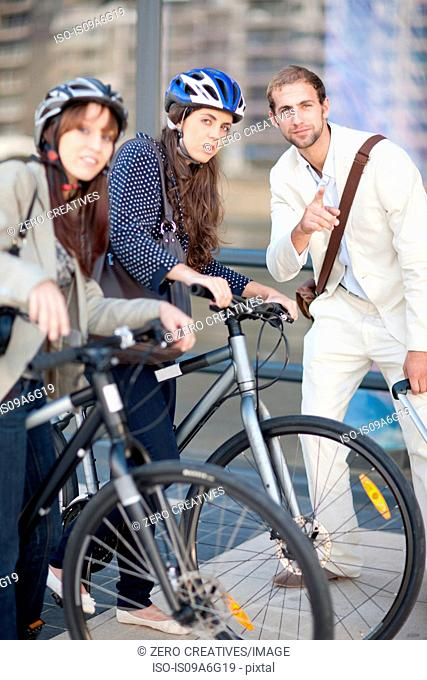 Young women with bicycles asking young man for directions