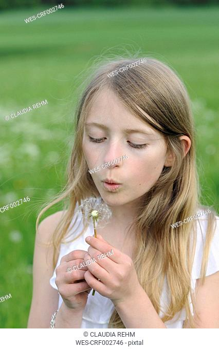 Portrait of girl blowing blowball