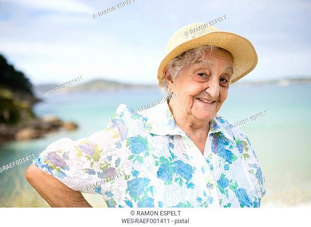 Portrait of smiling senior woman wearing straw hat
