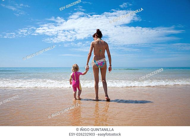 summer back family of two years old blonde baby with pink and yellow swimsuit holding hand with brunette woman mother in bikini standing at sea shore beach sand...