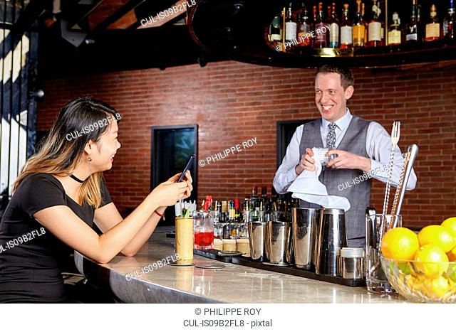 Woman in bar talking with bartender