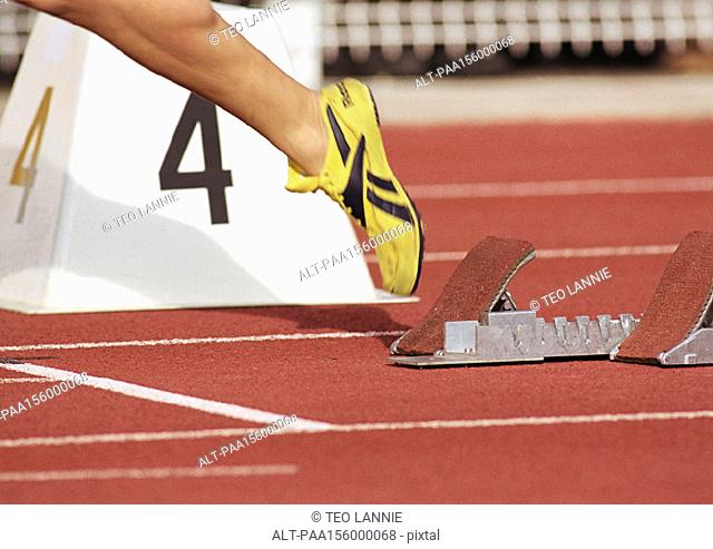 Runner leaving starting block, low section, close-up