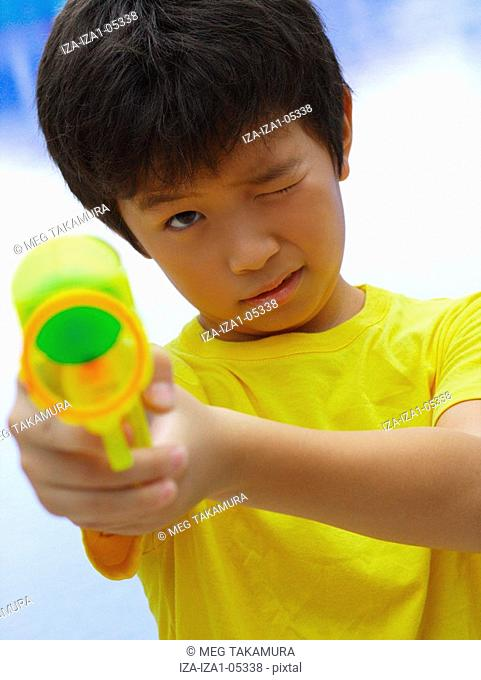 Portrait of a boy aiming a squirt gun