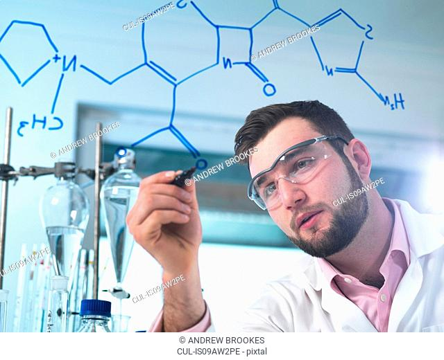 Scientist illustrating antibiotic chemical formula in laboratory for pharmaceutical research