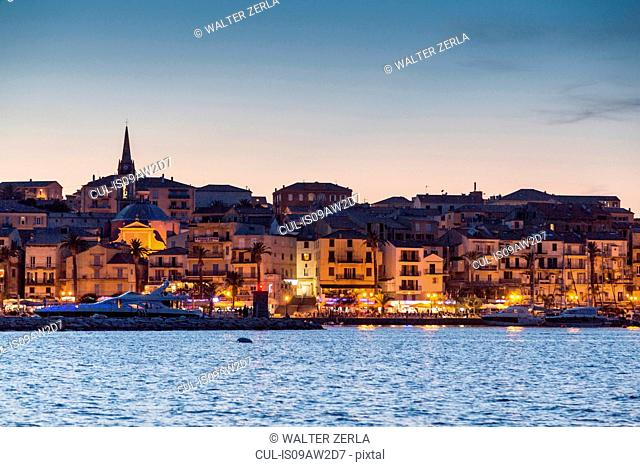 View of sea and Calvi city lights at dusk, Corsica, France