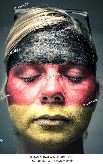 Portrait of woman with flag of Germany painted on face and closed eyes