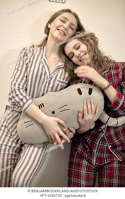two friends in pyjamas with plushie