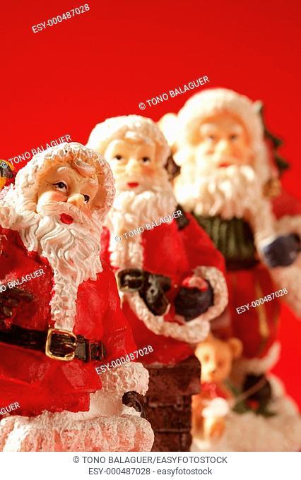 Three Santa Claus figurines over red background, studio shot
