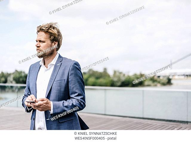 Businessman standing on bridge holding cell phone