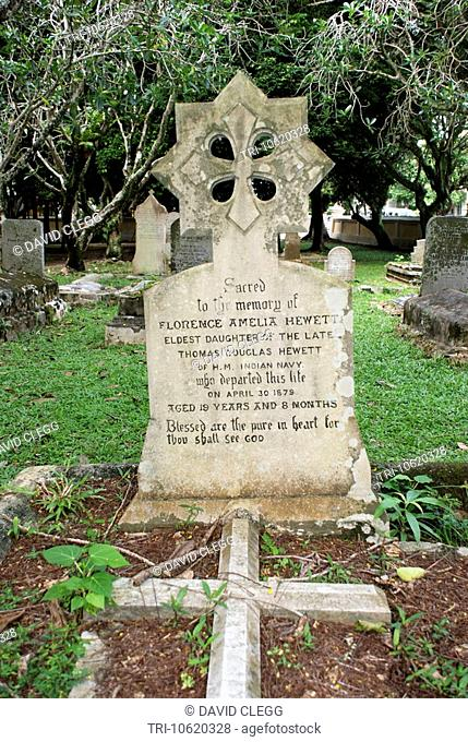 Carved headstone at the grave of daughter of Her Majesties Indian Navy personnel died 1879 aged 19 years Protestant Cemetary other graves and trees in...