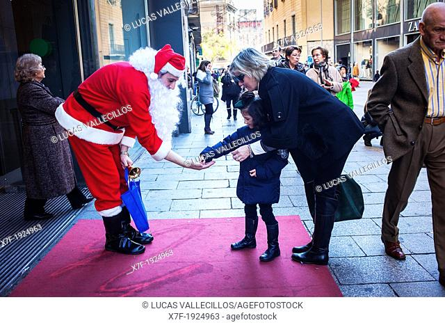 Santa Claus giving candy to a girl, in Avinguda del Portal de l'Angel  Barcelona  Catalonia, Spain