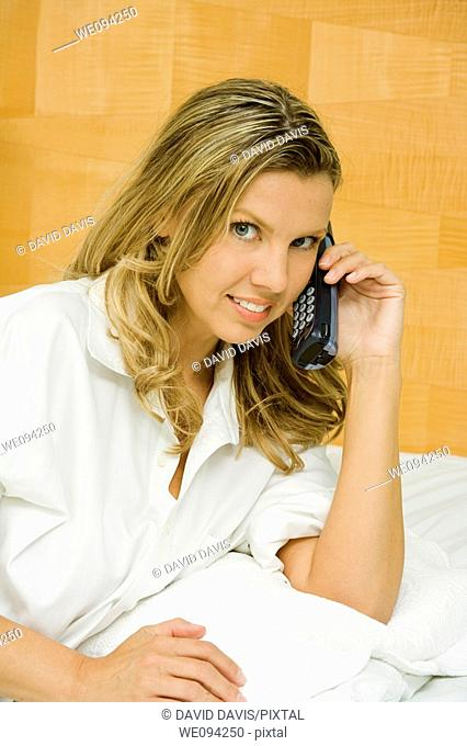 Beautiful caucasian woman setting in bed talking on the phone