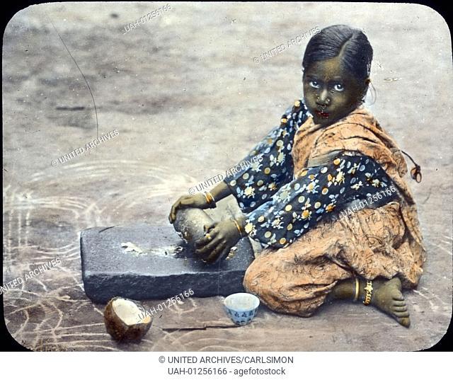 India, little girl preparing Curry, image date: circa 1910. Carl Simon Archive