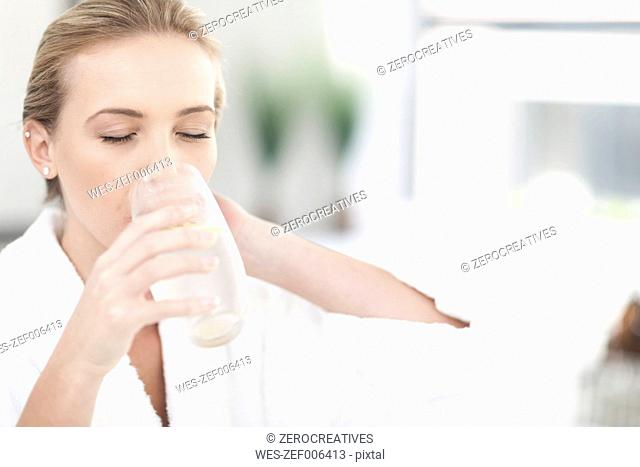Woman drinking glass of water in a spa