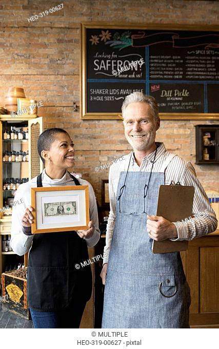 Portrait confident spice shop owners holding framed first dollar bill