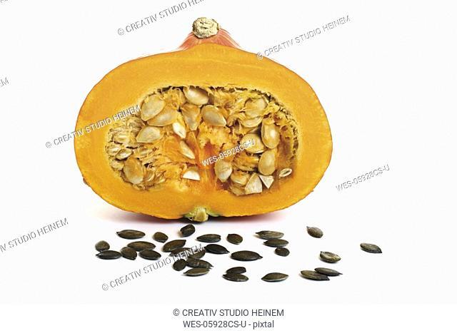 Half a pumpkin, pumpkin seeds in front