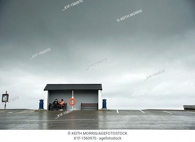 two people sheltering from the rain, Aberaeron Wales UK