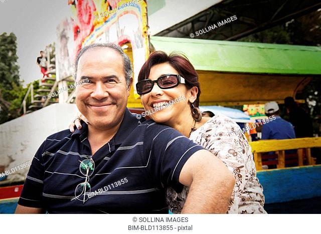 Hispanic couple smiling at amusement park