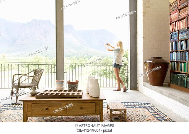 Woman taking picture of landscape from balcony