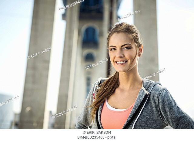 Smiling Caucasian woman posing under overpass