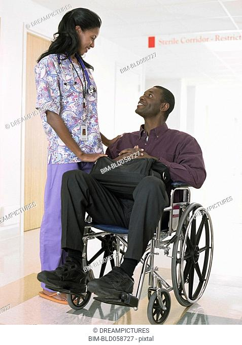African female nurse looking at patient in wheelchair