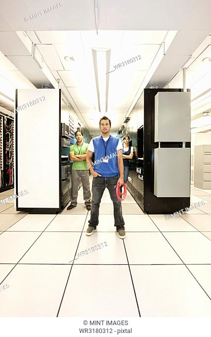 Portrait of three multi-ethnic technicians who work in a large computer server room